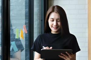una empleada de la empresa utiliza una tableta y un bloc de notas para analizar los presupuestos de la empresa foto