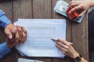 El agente de bienes raíces o el funcionario bancario describe el interés del préstamo al cliente. foto