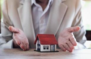 El agente inmobiliario le da una casa modelo al cliente para que firme el contrato. foto