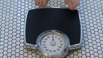 Woman stepping onto scale video