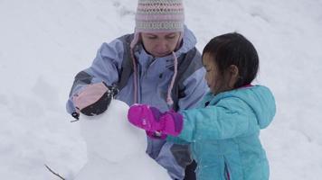 mãe e filha construindo um boneco de neve juntas video