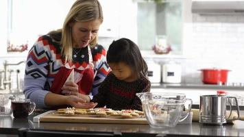 Mother and daughter frosting gingerbread cookies video