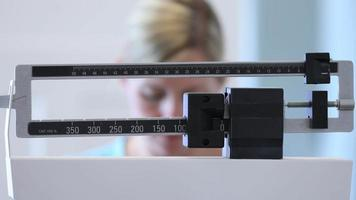 Woman weighing herself on scale video