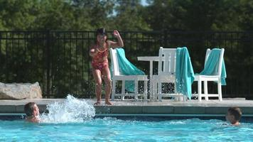 Girl jumping into pool in super slow motion video