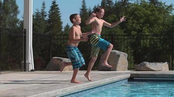 dos niños saltando a la piscina en cámara super lenta video