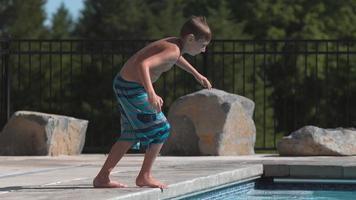 niño haciendo una voltereta en la piscina en cámara super lenta video