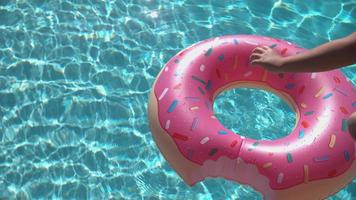 Girl jumping onto inflatable doughnut in super slow motion video