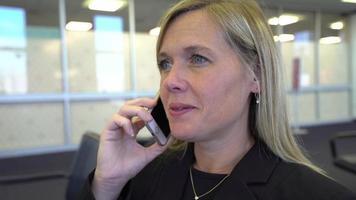 donna d'affari che parla al cellulare in aeroporto video