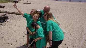 voluntários tirando fotos juntos na limpeza da praia video
