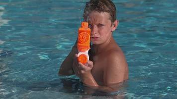 Closeup of boy spraying water gun in super slow motion video