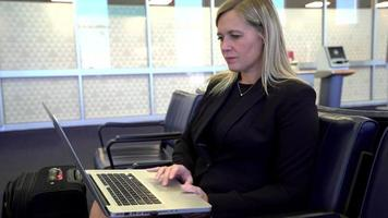 Business woman using laptop computer at airport video