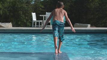 Boy jumping into pool in super slow motion video