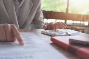 El empresario con la calculadora para calcular el presupuesto y los documentos de préstamo en la oficina foto