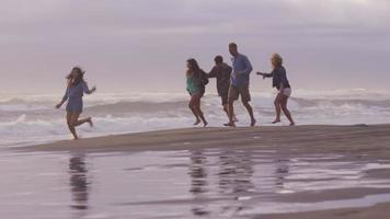 Group of friends at beach running in surf video