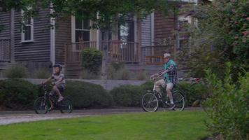 Senior man and grandson riding bicycles together video