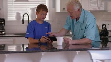 kleinzoon laat grootvader zien hoe tablet te gebruiken video