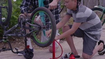 Senior man and grandson fixing bicycle together video