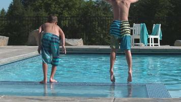 Kids jumping into pool in super slow motion video