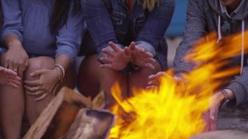 Group of friends at beach warming up hands by campfire video