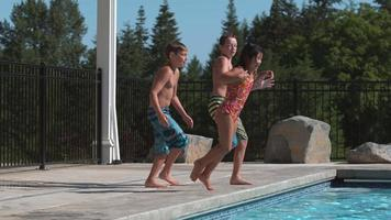 Three kids jumping into pool in super slow motion video