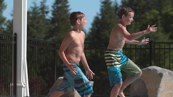 Two boys jumping into pool in super slow motion video