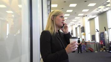 donna d'affari che usa il cellulare in aeroporto video