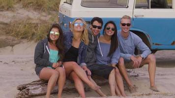 Portrait of friends sitting on log at beach with vehicle in background video