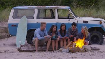Group of friends at beach hanging out by campfire video
