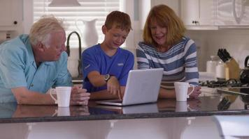 Grandson showing grandparents how to use computer video