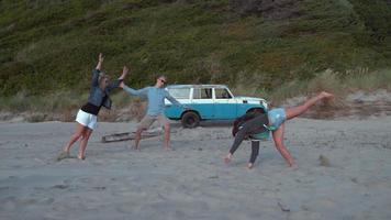 super slow motion skott av en grupp vänner som gör karthjul på stranden, skott med fantom flex 4k video