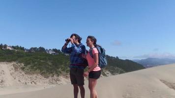 Par de caminatas sobre las dunas de arena en la playa, deténgase para mirar a través de binoculares video