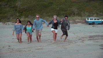 super slow motion skott av en grupp vänner som kör på stranden, skott med fantom flex 4k video