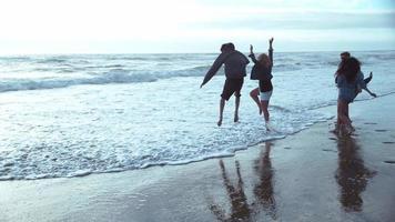super slow motion skott av grupp av vänner hoppar in i surf, skott med fantom flex 4k video