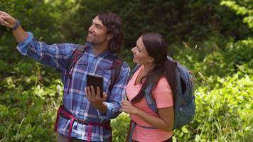 couple faisant de la randonnée et utilisant une tablette pour parcourir les sentiers video