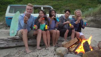 Group of friends at beach hanging out by campfire blowing bubbles video