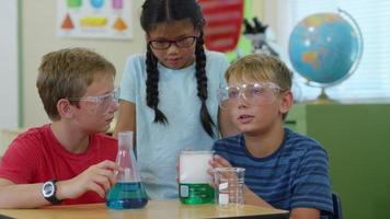 Three kids in classroom looking at science experiment video