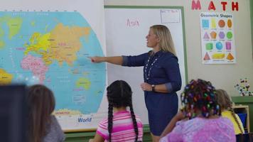 professor dá aula na sala de aula e os alunos levantam as mãos video