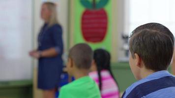 professor dá aula na sala de aula e os alunos levantam as mãos, concentre-se nas mãos das crianças video