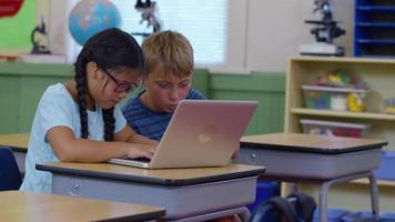 duas crianças na sala de aula trabalhando em um laptop video