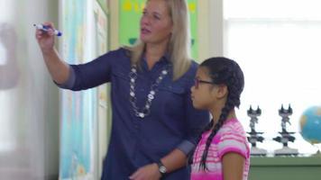 El estudiante va al frente de la clase y escribe en la pizarra en el aula de la escuela. video