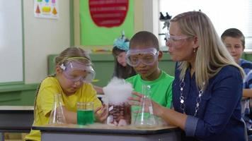 Teacher and students doing science experiment in school classroom video