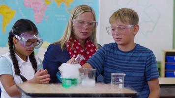 Teacher doing science experiment with students in school classroom video