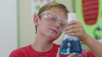 Boy in school classroom looking at bubbling science experiment video