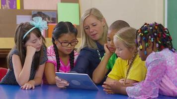 leraar en groep studenten kijken samen naar digitale tablet in de klas op school video