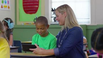 leraar en student kijken naar digitale tablet in schoolklas video
