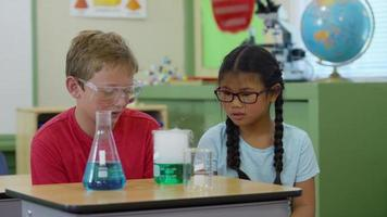 Two students in classroom looking at science experiment video