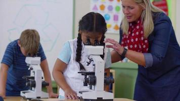 Teacher helping student with microscope in school classroom video