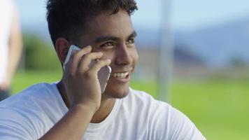 giocatore di basket adolescente parlando al cellulare al campo all'aperto video