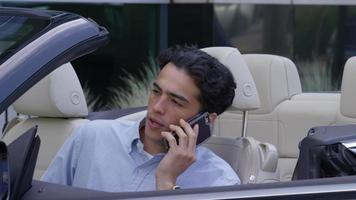 giovane uomo d'affari seduto in macchina che parla al cellulare video