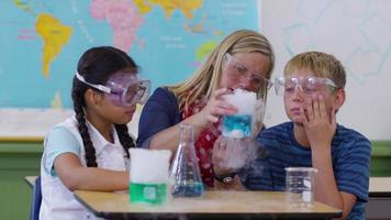 Teacher and students in school classroom with science experiment video